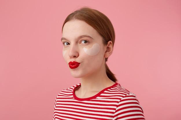 Portrait de jolie jeune fille rousse souriante aux lèvres rouges et avec des taches sous les yeux, porte un t-shirt rayé rouge, regarde et envoie un baiser, se dresse.