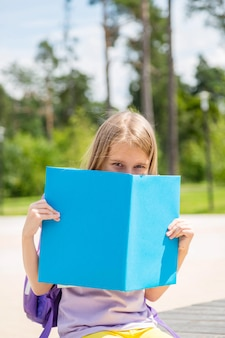 Portrait d'une jolie jeune fille se cachant derrière un livre ouvert