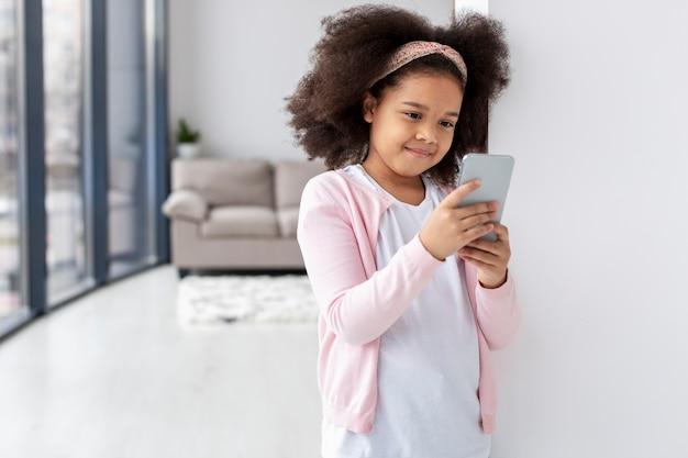 Portrait de jolie jeune fille tenant un téléphone mobile