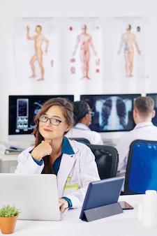Portrait de jolie jeune médecin positif assis à table en laboratoire de cliniques et travaillant sur ordinateur portable