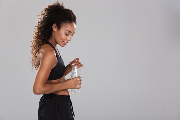 Portrait d'une jolie jeune sportive africaine au repos après une formation isolée sur un mur gris, tenant une bouteille avec de l'eau