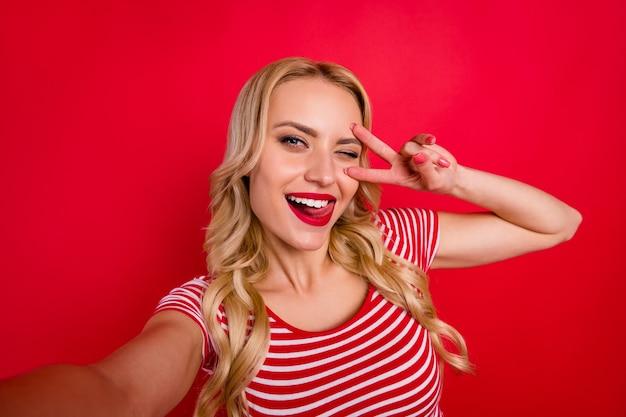 Portrait de jolie jolie fille blogueuse faire clignoter les dents de lécher les dents du signe v selfie