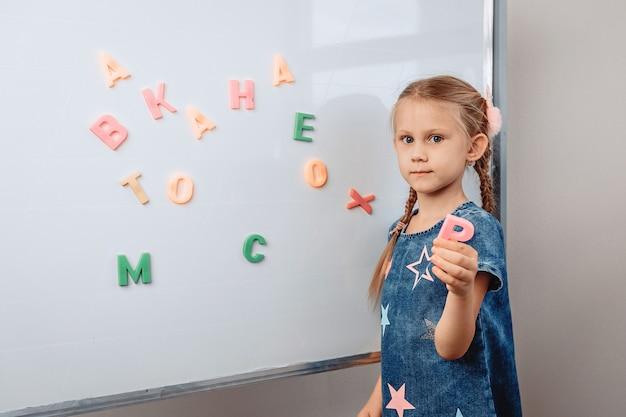 Portrait d'une jolie jolie fille développée debout en face d'un tableau blanc en lettres de l'alphabet dispersées et montrant la lettre p. concept de développement de l'enfant. photo avec noise.photo avec bruit