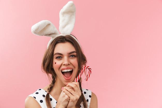 Portrait d'une jolie jolie fille portant des oreilles de lapin debout isolé, grimaçant, tenant la canne à sucre