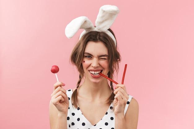 Portrait d'une jolie jolie fille portant des oreilles de lapin debout isolé, grimaçant, tenant une sucette