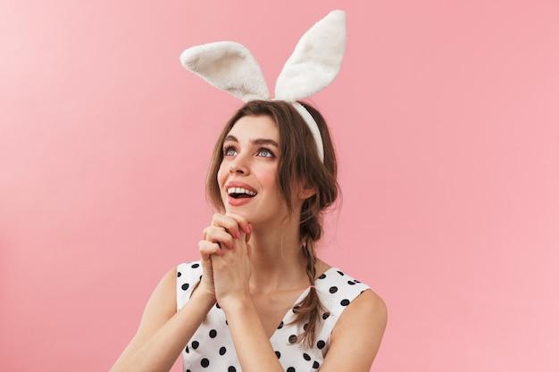 Portrait d'une jolie jolie fille portant des oreilles de lapin debout isolé, la mendicité