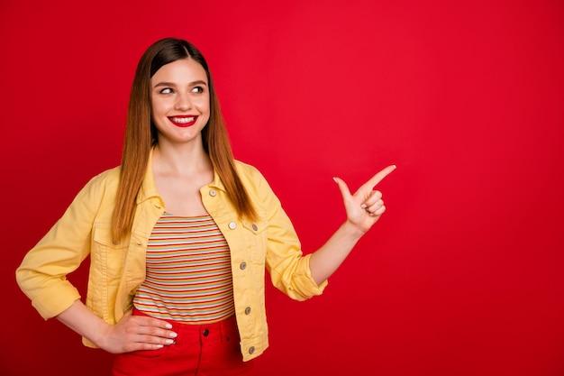 Portrait d'une jolie jolie fille rousse gaie et gaie vêtue d'une publicité décontractée montrant une copie de l'espace vide isolée sur un fond de couleur rouge vif et brillant
