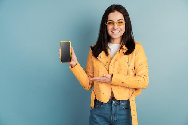 Portrait de jolie jolie fille tenant en main un smartphone avec écran blanc