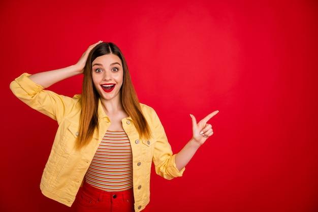 Portrait d'une jolie jolie jolie chanceuse étonnée, joyeuse, joyeuse et gaie, fille aux cheveux roux montrant une publicité pour l'espace de copie isolée sur un fond de couleur rouge vif brillant