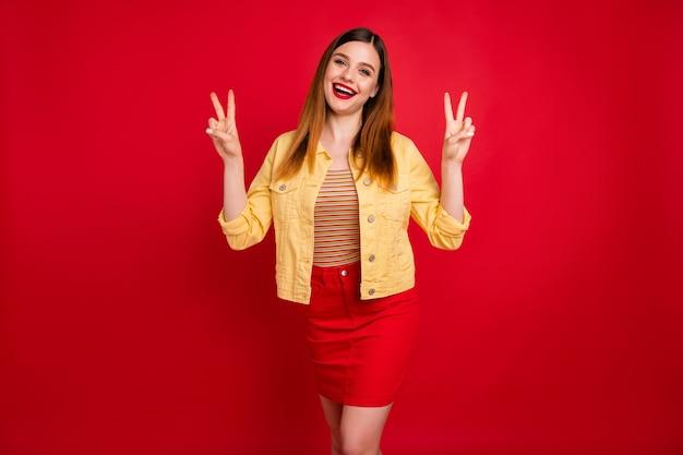 Portrait d'une jolie jolie jolie jolie charmante à la mode heureuse gaie joyeuse fille rousse montrant un double signe v s'amusant isolé sur fond de couleur rouge vif éclatant