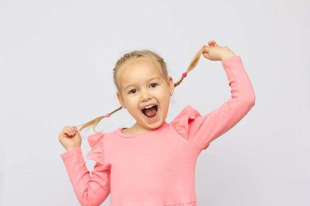 Portrait d'une jolie jolie jolie jolie fille adorable gaie gaie positive drôle d'écolière jouant avec des boucles bouche ouverte isolée sur fond blanc