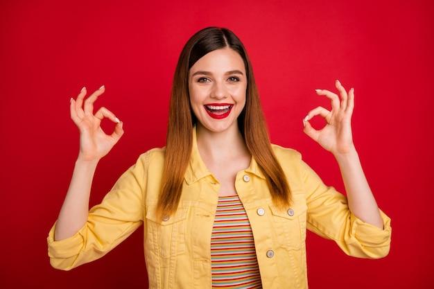 Portrait d'une jolie jolie jolie jolie fille aux cheveux roux gaie et gaie montrant deux publicités double signe ok isolées sur fond de couleur rouge vif éclatant