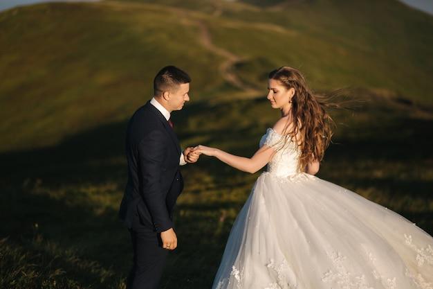 Portrait de jolie mariée et marié élégant profitant de moments romantiques dans les montagnes au coucher du soleil