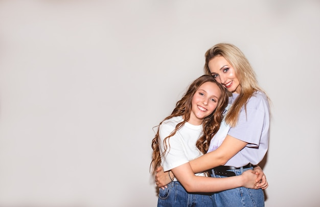 Portrait de jolie mère blonde et jolie adolescente aux longs cheveux bouclés posant près du mur blanc