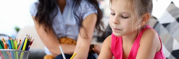 Portrait de jolie mère enseignant la peinture petit enfant. belle femme souriante, passer du temps heureux avec sa fille à la maison.