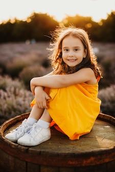 Portrait d'une jolie petite fille assise sur un tonneau regardant la caméra en riant tout en nettoyant sa main sur ses jambes contre le coucher du soleil dans un champ de lavande.