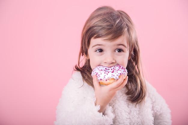 Portrait de jolie petite fille avec beignet