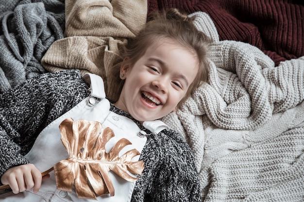 Portrait d'une jolie petite fille dans un pull avec une feuille dans ses mains.
