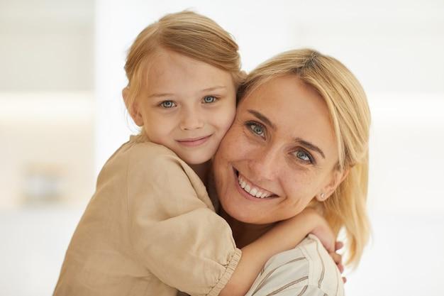 Portrait de jolie petite fille embrassant une mère heureuse avec amour souriant