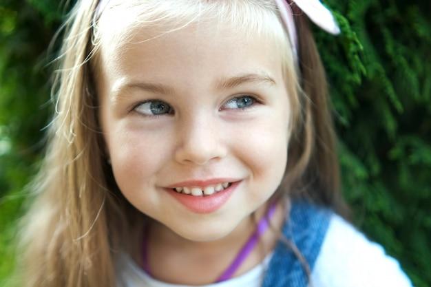 Portrait de jolie petite fille enfant debout à l'extérieur dans le parc d'été souriant joyeusement.