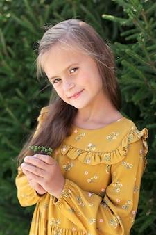 Portrait d'une jolie petite fille à l'extérieur en été, le bébé tient une fleur dans ses mains et sourit. le concept d'une vie heureuse..