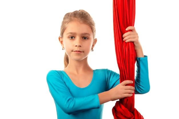 Portrait d'une jolie petite fille gymnaste dans un maillot de bain bleu tenant un ruban d'air en soie sur fond blanc