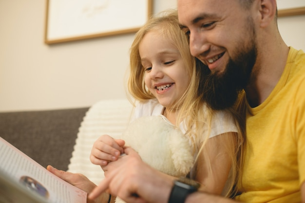 Portrait d'une jolie petite fille lisant un livre avec son jeune père barbu le matin sur le canapé à la maison.