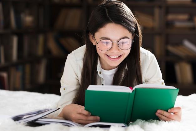Portrait de jolie petite fille lisant un livre