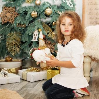 Portrait d'une jolie petite fille parmi les décorations de noël