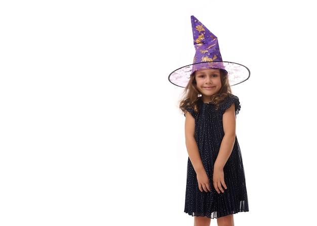 Portrait d'une jolie petite fille portant un chapeau de sorcier et vêtue d'une élégante robe de carnaval, regardant la caméra posant les bras croisés sur fond blanc. concept d'halloween avec espace de copie
