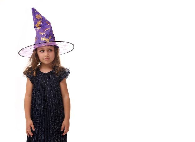 Portrait d'une jolie petite fille portant un chapeau de sorcier et vêtue d'une élégante robe de carnaval, regardant la caméra posant les bras croisés sur fond blanc, espace de copie. notion d'halloween