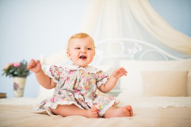 Portrait d'une jolie petite fille potelée aux cheveux blonds dans une robe assise sur un grand lit
