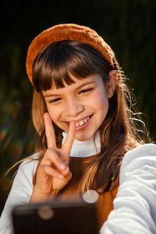 Portrait de jolie petite fille prenant un selfie