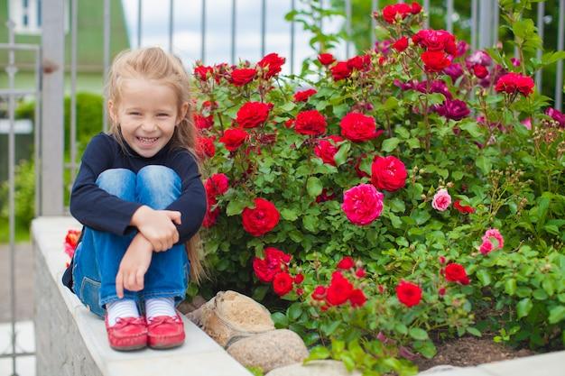 Portrait de jolie petite fille près des fleurs dans la maison de jardin