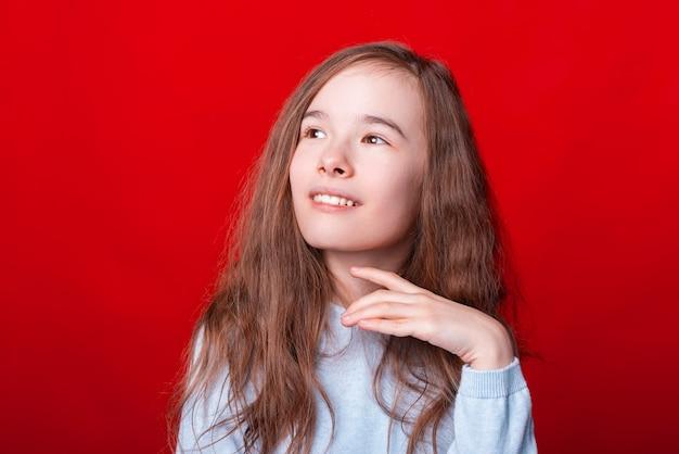 Portrait de jolie petite fille à la recherche de suite sur le mur rouge