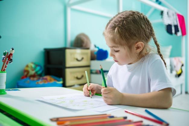 Portrait d'une jolie petite fille regardant la caméra et souriant tout en dessinant des images ou en faisant ses devoirs, assise à une table à l'intérieur de la maison, espace de copie