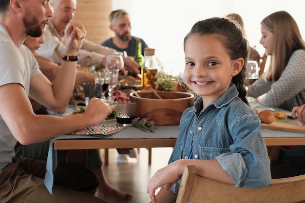 Portrait de jolie petite fille souriante assise sur une chaise et en train de dîner avec sa grande famille