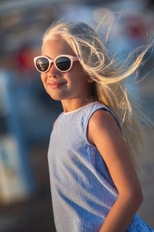 Portrait d'une jolie petite fille souriante avec des lunettes.une fille en short et un t-shirt bleu au coucher du soleil au bord de la mer.turquie