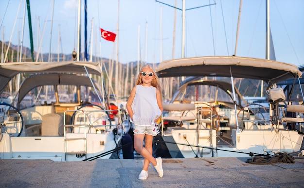 Portrait d'une jolie petite fille souriante avec des lunettes sur une jetée avec des yachts.une fille en short et un t-shirt bleu au coucher du soleil près des yachts.turquie.