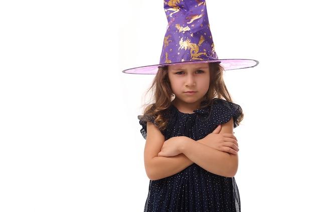 Portrait d'une jolie petite sorcière en colère en colère portant un chapeau de sorcier et vêtue d'une élégante robe de carnaval, regardant la caméra posant les bras croisés sur fond blanc, espace de copie. halloween