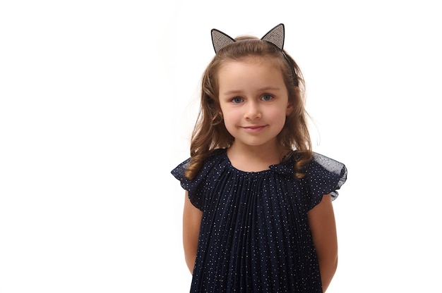 Portrait d'une jolie petite sorcière souriante portant un cerceau avec des oreilles de chat, vêtue d'une élégante robe de carnaval, regardant la caméra posant les bras croisés sur fond blanc, espace pour copie, halloween