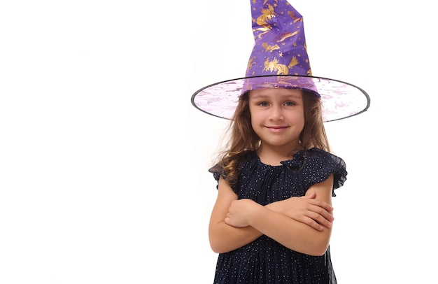 Portrait d'une jolie petite sorcière souriante portant un chapeau de sorcier et vêtue d'une élégante robe de carnaval, regardant la caméra posant les bras croisés sur fond blanc, espace pour copie, halloween