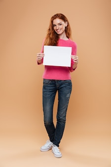Portrait d'une jolie rousse joyeuse tenant une pancarte blanche vierge