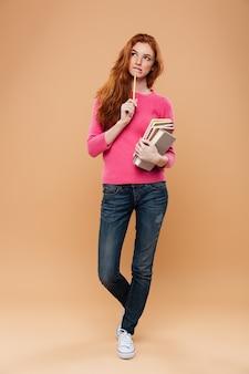 Portrait d'une jolie rousse pensive tenant des livres