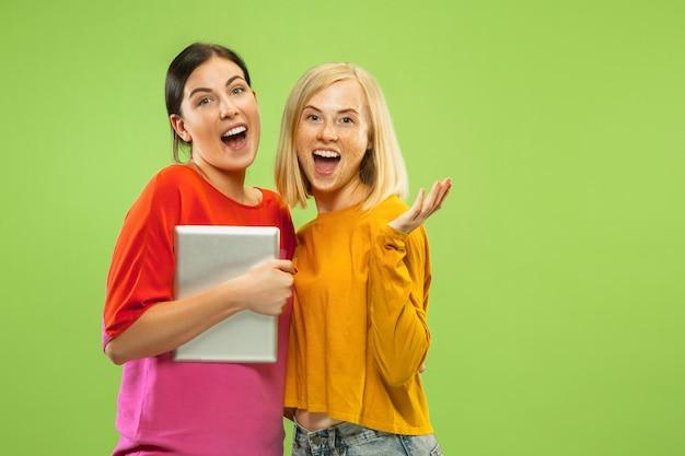 Portrait de jolies filles charmantes dans des tenues décontractées isolées sur fond de studio vert. copines ou lesbiennes utilisant une tablette pour s'amuser ou pour payer. concept de lgbt, émotions humaines, amour, relation.