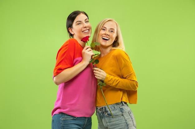 Portrait de jolies filles charmantes dans des tenues décontractées isolées sur le mur de studio vert