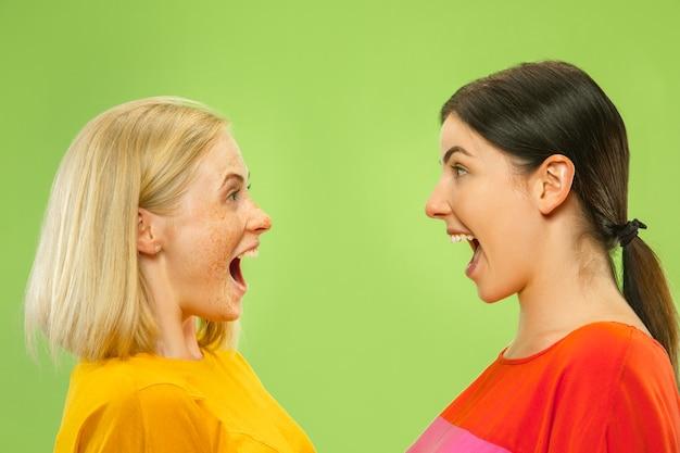 Portrait de jolies filles charmantes dans des tenues décontractées isolées sur un mur vert. deux modèles féminins en copines ou lesbiennes. concept de lgbt, égalité, émotions humaines, amour, relation.