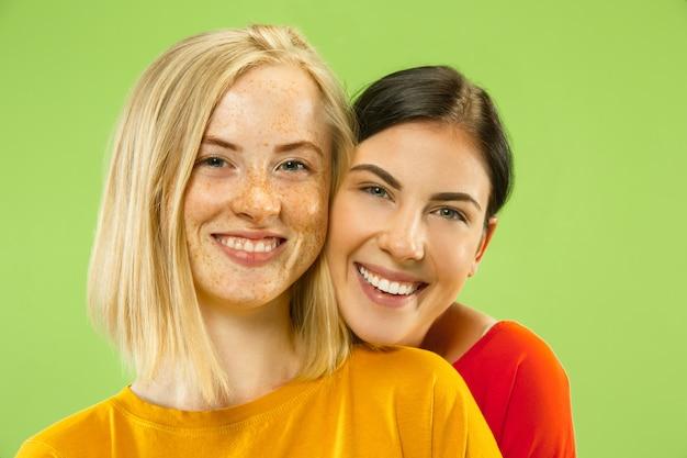 Portrait de jolies filles charmantes dans des tenues décontractées isolés sur vert