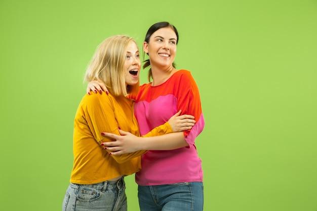 Portrait de jolies filles charmantes en tenues décontractées sur studio vert