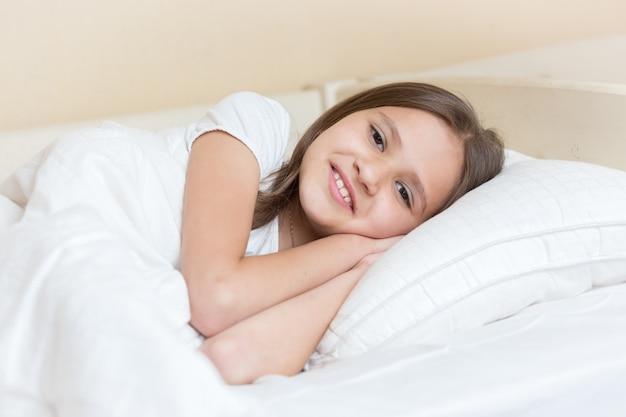 Portrait de jolies filles souriantes allongées sur un oreiller
